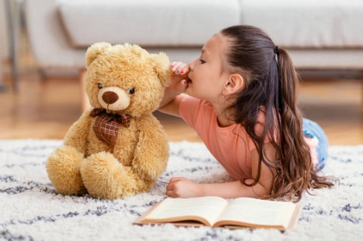 Mädchen redet mit Plüschbär