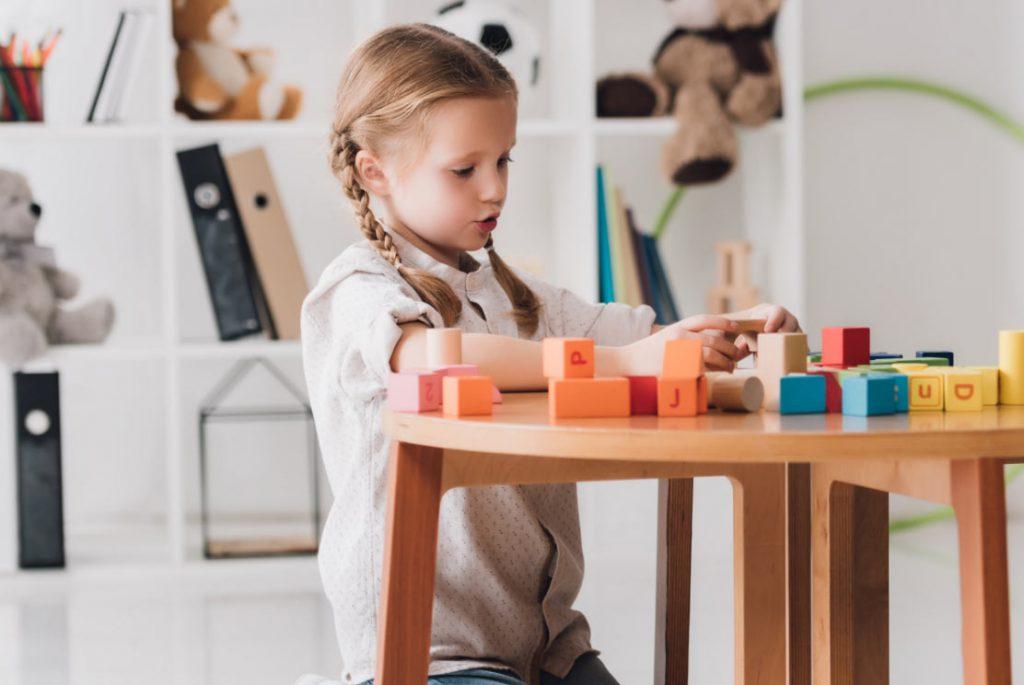 Mädchen spielt mit Buchstaben-Klötzchen
